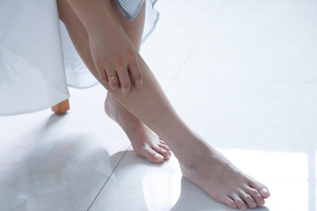 Žena si drží pravú nohu, ktorú ma položenú na bielej podlahe