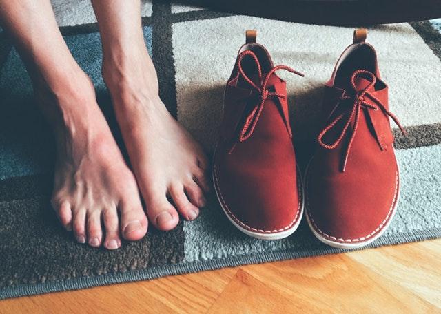 Bosé nohy, vedľa ktorých sú položené červené topánky
