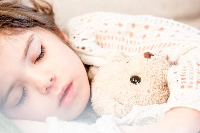 Malé dievča v pletenom svetri spí s plyšovým medveďom.jpg