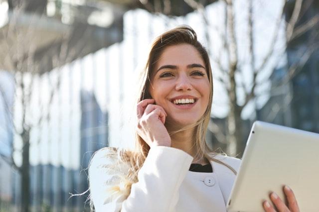 Žena sa pozerá do tabletu a telefonuje